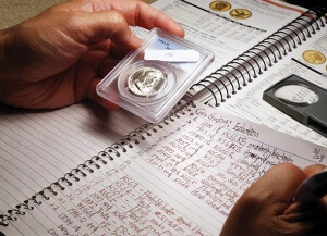 someone holding a coin with a notebook