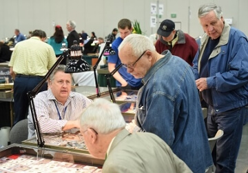 people at a booth at a coin show