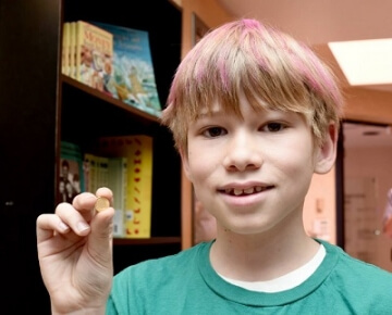 young boy holding a small coin