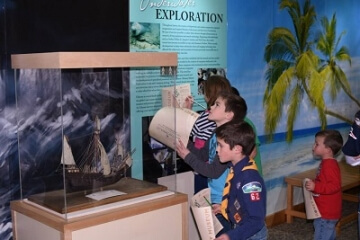 people looking at a model ship in a display case