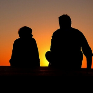 two people silhouetted against a sunset