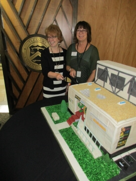 two women with a model of a building