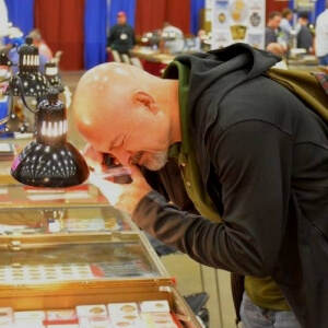 man bent over booth at coin show