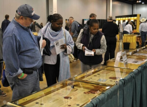 coin show attendees viewing collector exhibit